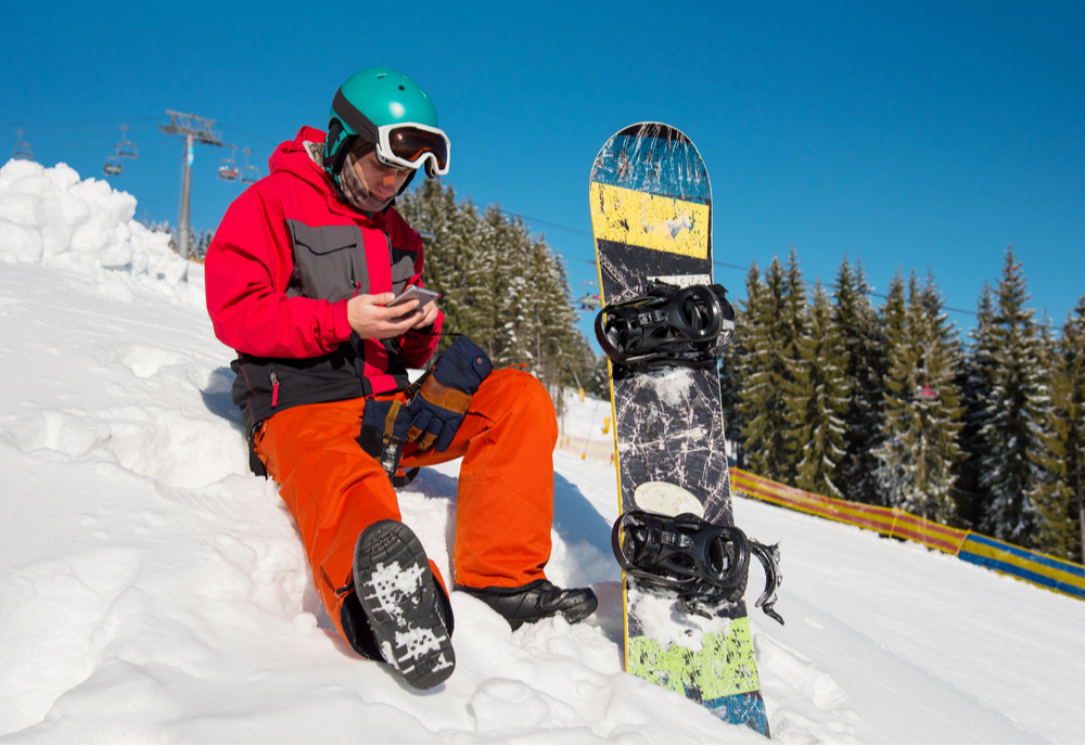 Person taking a break from skiing using mobile phone