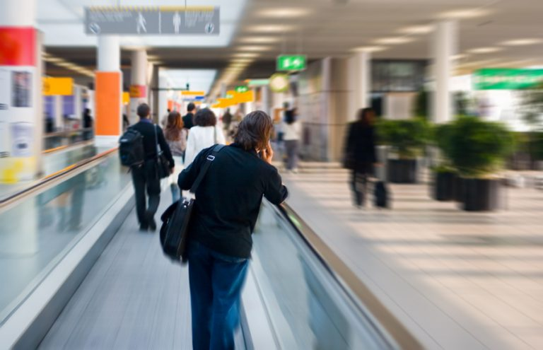 Person on phone travelling through airport