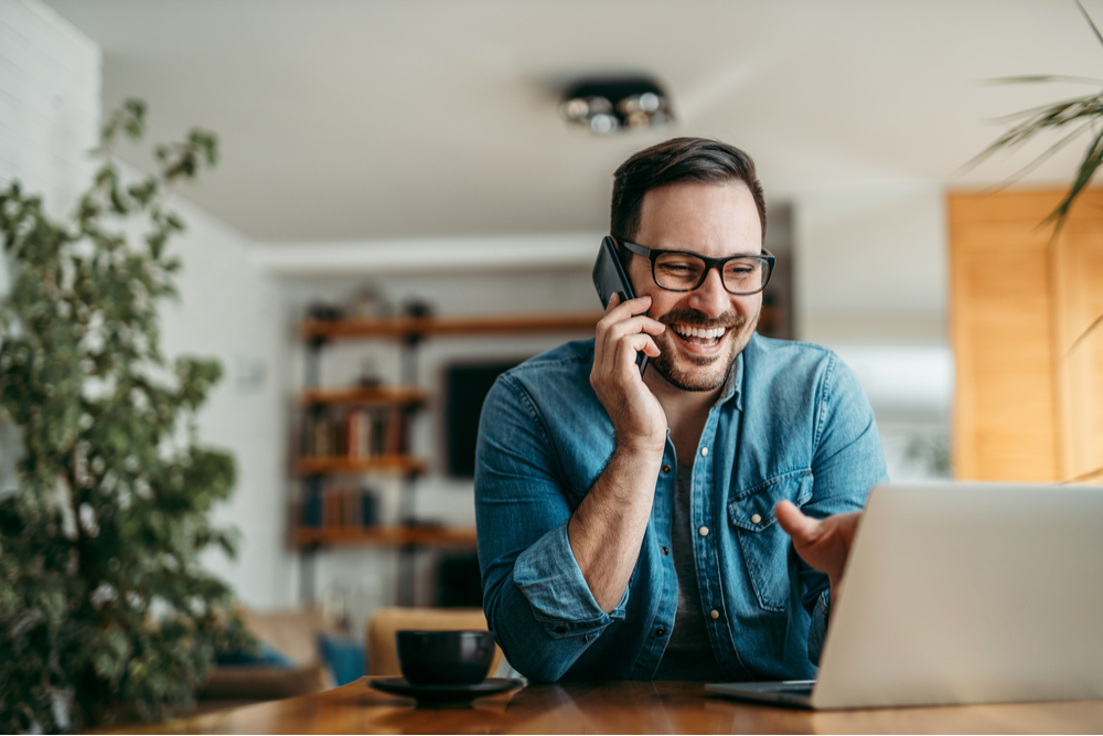 Man working from home happily chatting on the phone