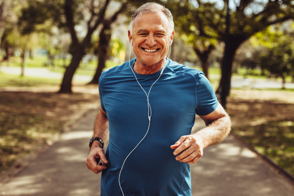 Close up of a smiling man running while listening to music using earphones.