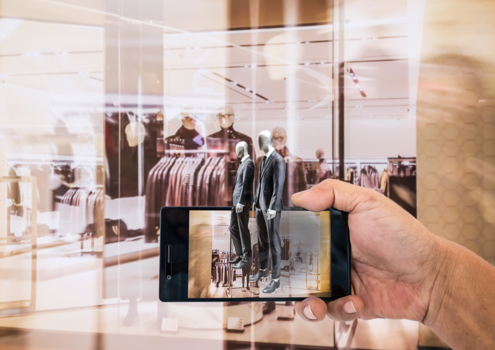 Hand holding smart phone with A/R application on screen to finding interested product in the store